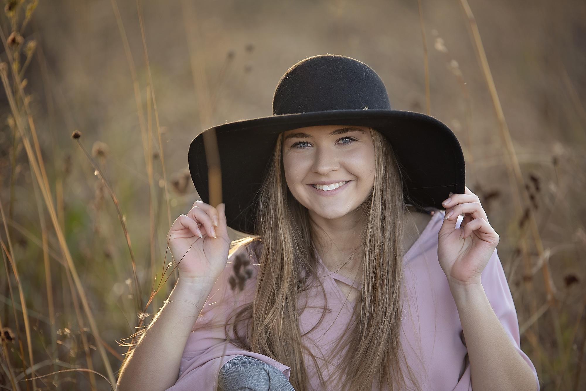 Fashion girl fun hat senior photo in prairie grass.