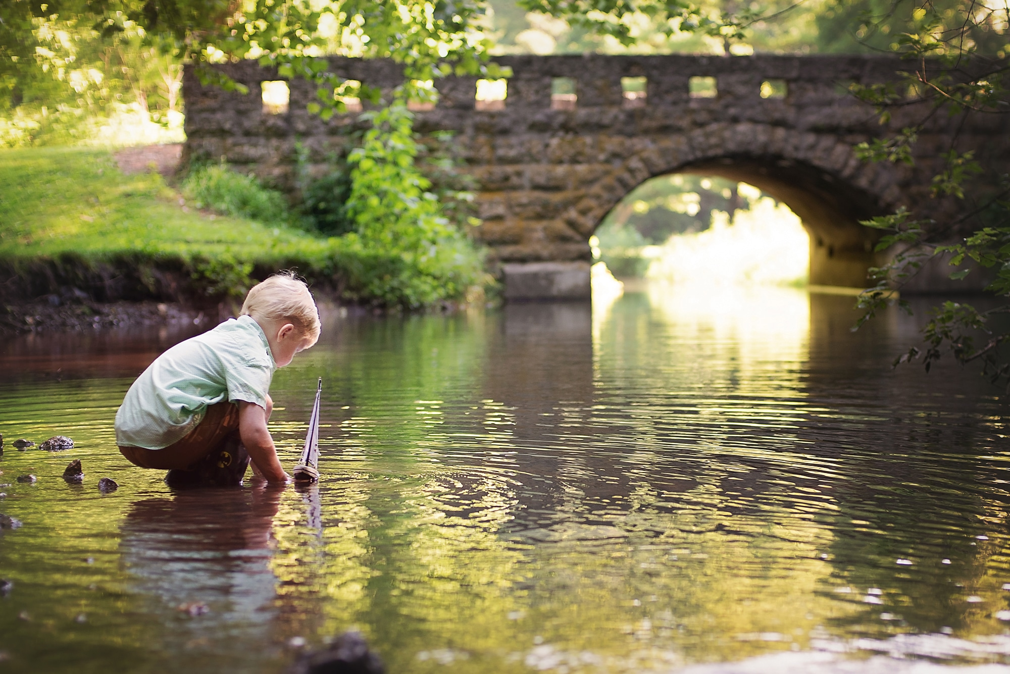 Boy playing with sailboat toy in creek