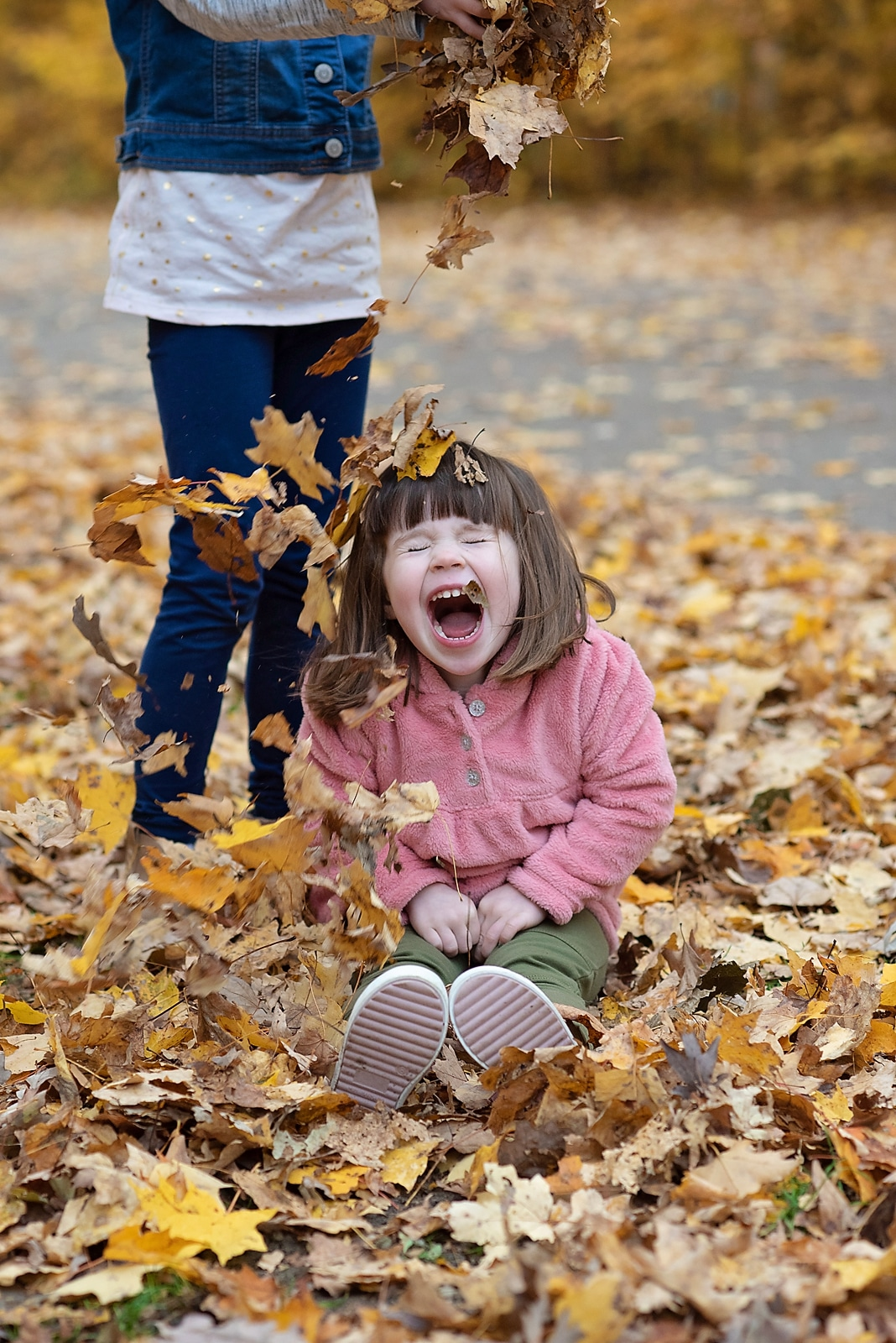 Sisters playing with leaves for photo shoot